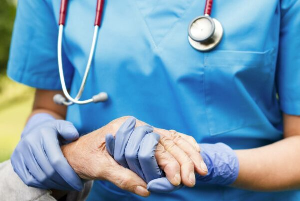 A close up photo of nurse with a stethoscope around their neck, wearing medical gloves, holding the hand of an elderly person.