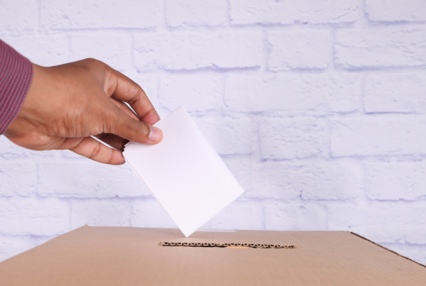 A man's hand dropping a ballot in a cardboard ballot box.