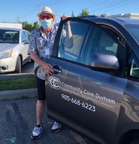 A Transportation driver wearing PPE standing next to an open van door.